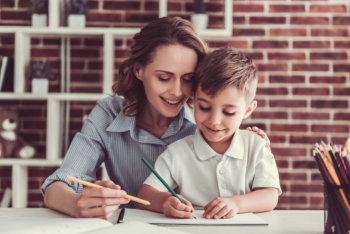 teacher helping her student write